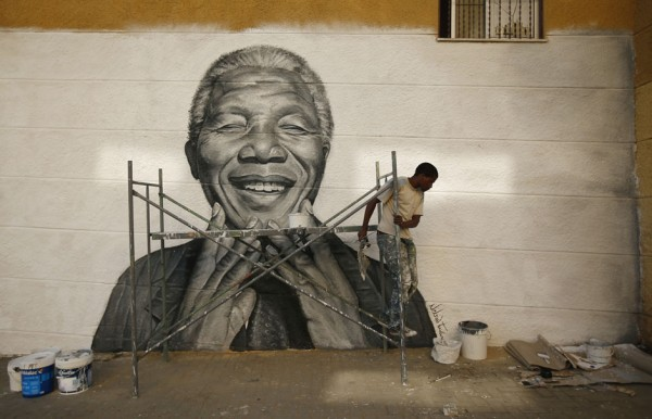 Tavares works on a graffiti of Nelson Mandela which he painted during festivities in his neighborhood in Lisbon
